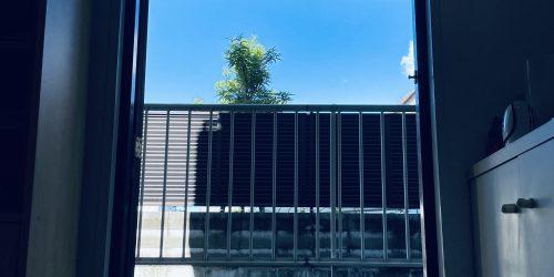 おうちの中から玄関外の青空が写っている