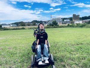 緑の芝生の上に車椅子に座っている僕