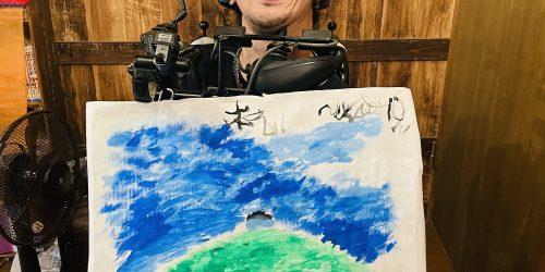 口に筆を咥えて描いた、緑の丘の上に人が立っていて青い空と白い雲のイラストを膝の上に乗っけて笑っている僕