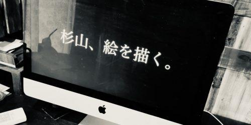 """パソコンに、""""杉山、絵を描く。""""という文字が写っているモノトーンの写真"""