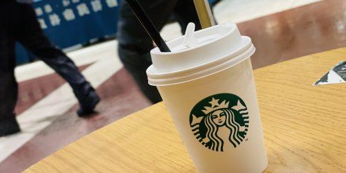 机の上に紙でできた容器に入っているスタバのコーヒー