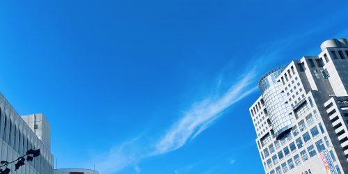 右手に駅ビルがありその上に青空が広がっている写真